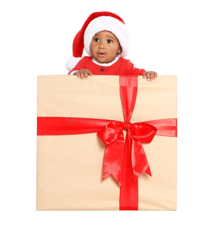 Festively dressed African-American baby in Christmas gift box on background royalty free stock images