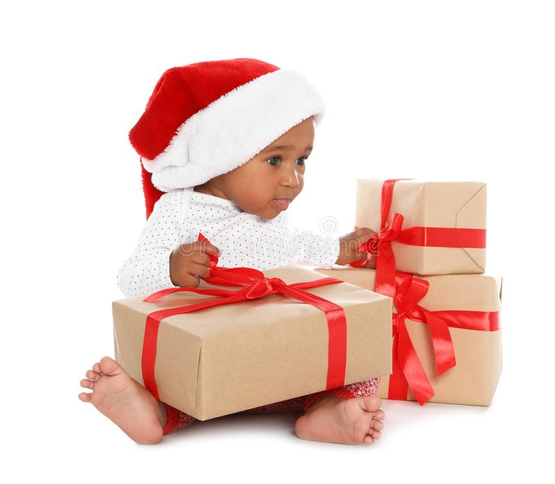 Festively dressed African-American baby with Christmas gifts stock photo