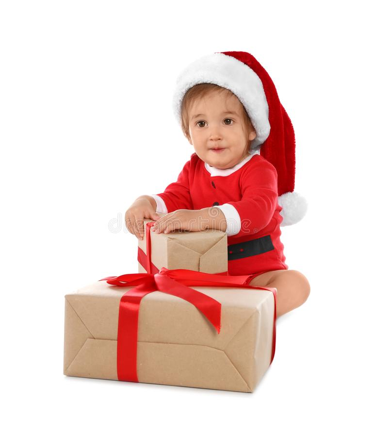 Festively dressed baby with gift boxes on white. Christmas celebration stock images