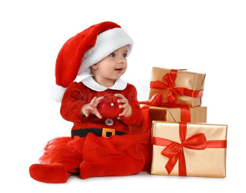 Festively dressed baby with gift boxes on white. Christmas celebration royalty free stock photography