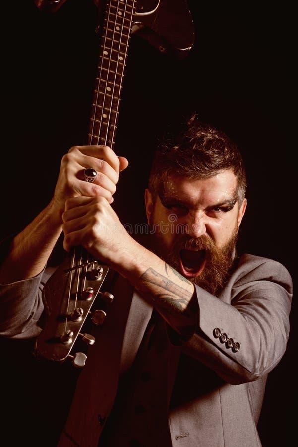 Festiwal Muzyki Gniewny mężczyzna z gitarą przy festiwalem muzyki Brodaty mężczyzna krzyk przy festiwalem muzyki Punk rock festiw zdjęcia stock