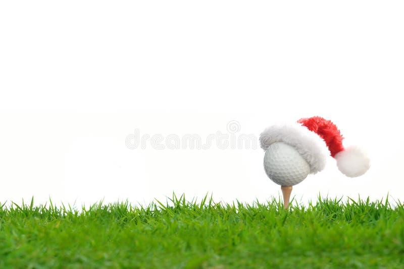 Festlich-aussehender Golfball auf T-Stück mit Weihnachtsmanns Hut stockfotografie