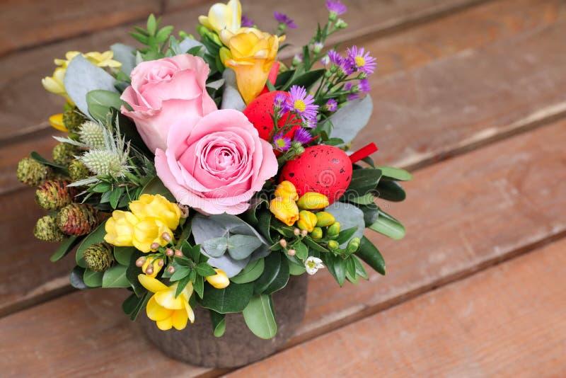Festliche Blumenanordnung für rosa Rosen, gelbe Freesieblumen, Eukalyptusblätter und andere Anlagen mit roten Ostereiern stockfotografie