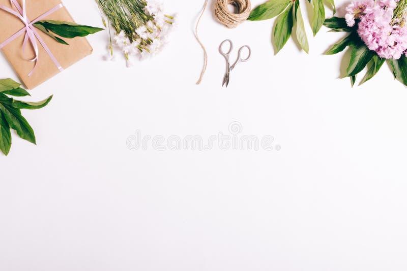 Festliche Blumenanordnung, -geschenke und -bänder auf einer weißen Tabelle lizenzfreie stockfotos