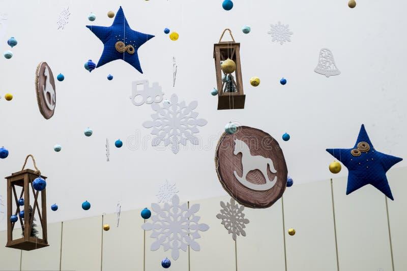 Festliche Dekoration des Raumes in der Art des neuen Jahres Blaue Sterne, Schneeflocken, Laternen, Pferde, Glocken und andere Spi lizenzfreies stockbild
