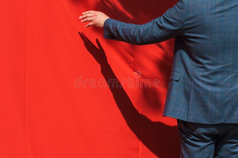 Festliche Eröffnung, Geschäftsmann öffnet roten Vorhang, um Produkt aufzudecken stockbilder
