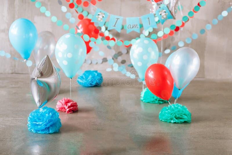 Festliche Hintergrunddekoration für Geburtstagsfeier, Buchstaben, die ein sagen und bunte Ballone im Studio, Kuchenzertrümmern lizenzfreie stockfotos