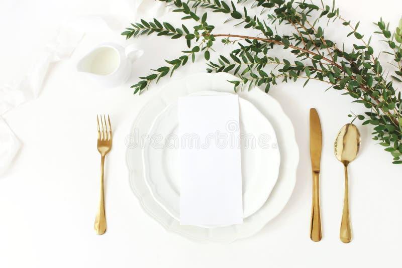 Festliche Hochzeit, Geburtstagsgedeck mit goldenem Tischbesteck, Eukalyptus parvifolia Niederlassung, Porzellanplatte, Milch und stockbilder
