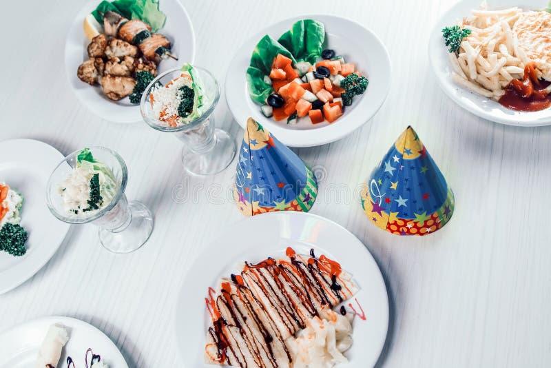 Festliche Kappen und eine Vielzahl von Tellern auf dem Tisch im Restaurant der Kinder stockfotos