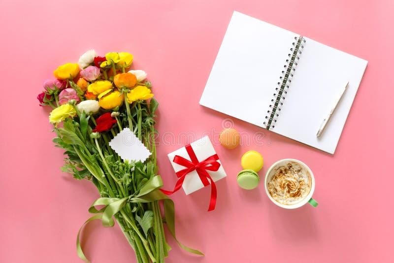 Festliche Morgenkonzeptbutterblume blüht Blumenstrauß, Geschenkbox, Schale Cappuccino, makarons zusammenbacken, sauberes Notizbuc stockbilder