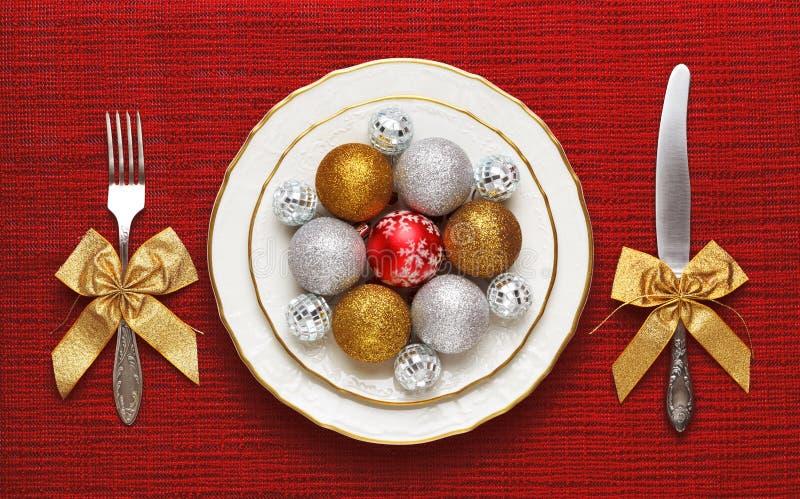 Festliche Umhüllung, auf einer weißen Platte sind Weihnachtsspielwaren Das Konzept des Silvesterabendabendessens stockbild
