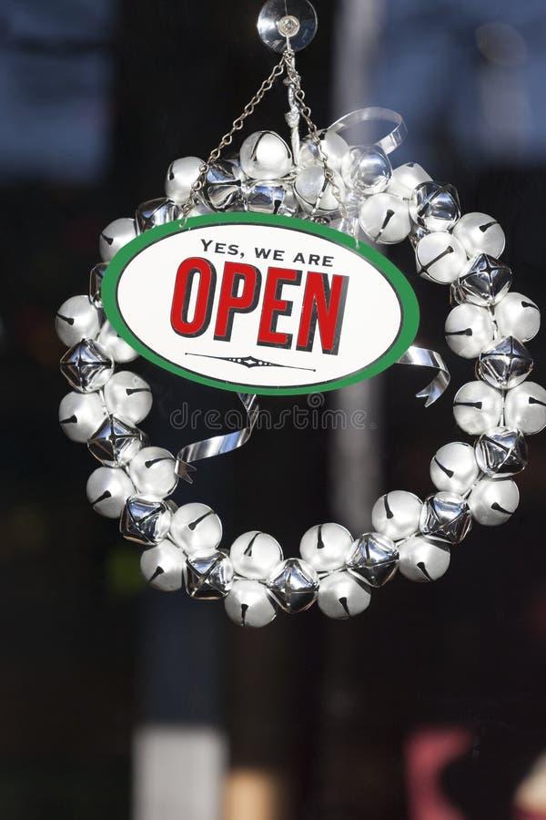 Festliche Weihnachtsdekorationen und offenes Zeichen mit Klingelglocke winden das Hängen in der Shopschaufenstertür Urlaubseinkäu stockfotos