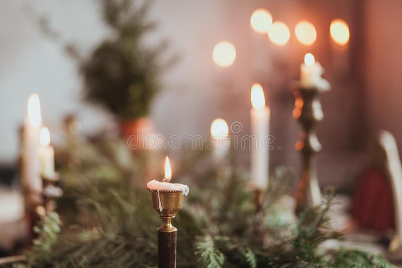 Festliche Weihnachtstischschmuckanordnung mit brennenden Kerzen und Tannenzweigen stockbilder