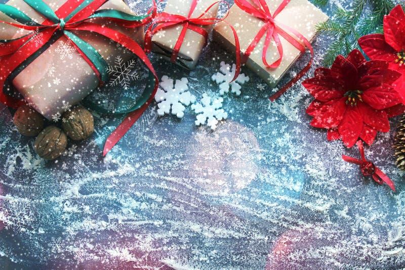 Festliche Weihnachtszusammensetzung mit Geschenken, Kästen, Kegel, Walnüsse, rote Blumen der Poinsettias auf einem hölzernen Hint stockbilder