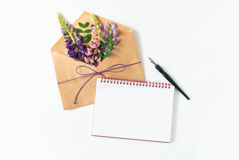 Festliche Zusammensetzung: auf einer weißen Tabelle liegt ein Umschlag, ein Notizbuch, ein Füllfederhalter und Blumen Konzept des stockbild