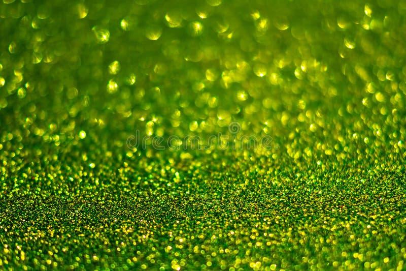 Festlicher abstrakter grüner Funkelnbeschaffenheitshintergrund mit glänzendem Schein Bunter defocused Hintergrund mit dem Funkeln lizenzfreie stockfotografie