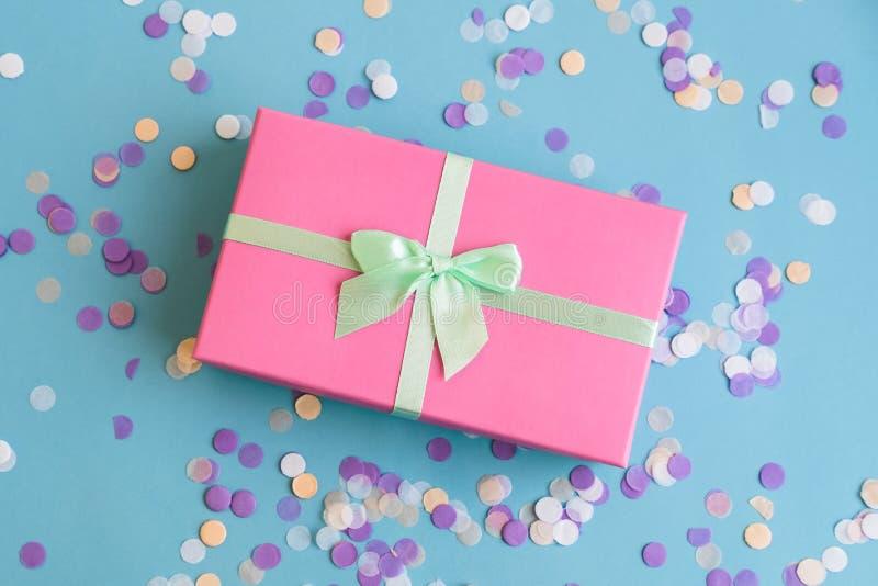 Festlicher Feiertag blauer Hintergrund neuen Jahres und Weihnachten mit rosa Geschenkbox, Konfetti Konzept des Karnevals, Geburts lizenzfreies stockfoto