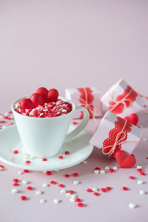 Festlicher Hintergrund Die Kaffeetasse, die vom Mehrfarbenbonbon voll ist, besprüht Zuckersüßigkeitsherzen und Verpackung Valenti lizenzfreies stockbild