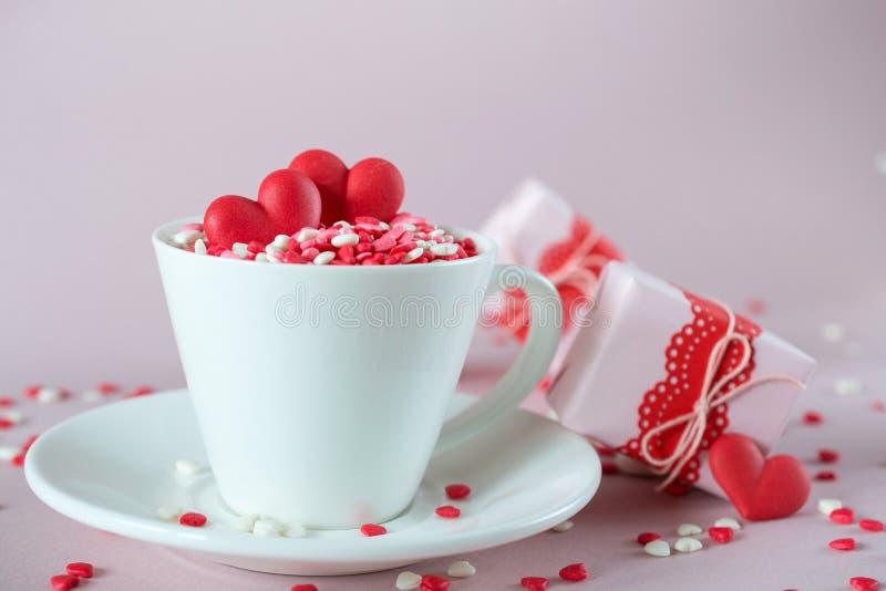 Festlicher Hintergrund Die Kaffeetasse, die vom Mehrfarbenbonbon voll ist, besprüht Zuckersüßigkeitsherzen und Verpackung Valenti lizenzfreie stockfotos