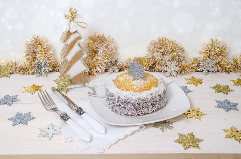 Festlicher Kürbiskuchen mit Kokosnuss auf Tabelle und Weihnachtsdekoration Hintergrund Bokeh stockfoto