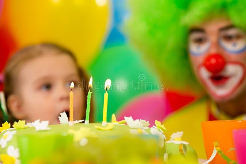 Festlicher Kuchen mit drei Kerzen, Kind mit Clown stockfotos