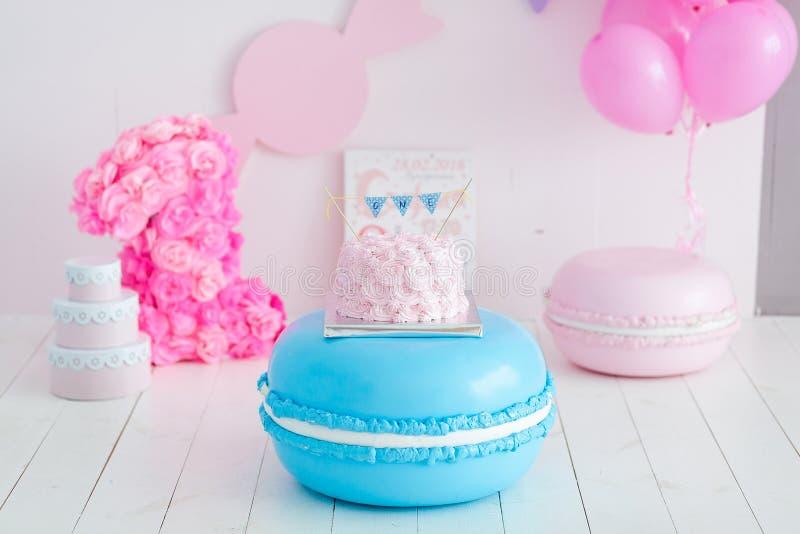 Festlicher Rosarose ombre Cremekuchen auf großer blauer Makrone Erstes Jahrkuchenzertrümmern lizenzfreie stockfotos