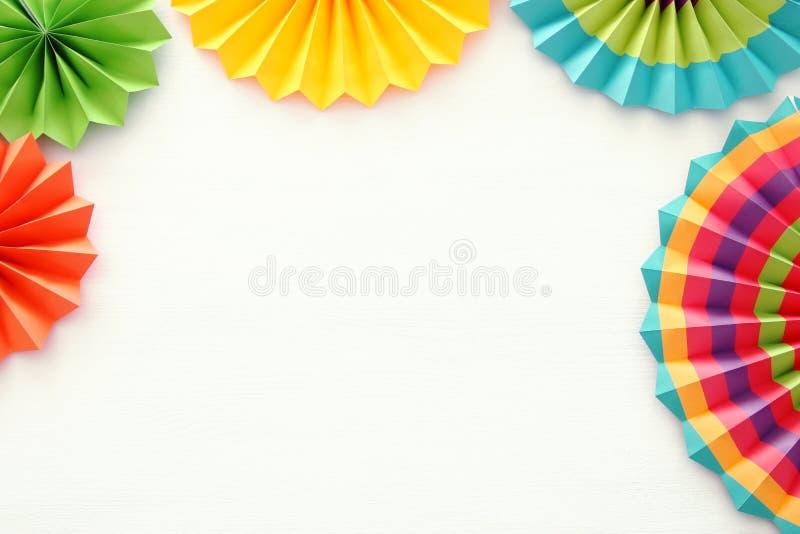 Festlicher und Parteihintergrund mit bunten Papierkreisfans über hölzernem weißem Hintergrund Kopieren Sie Platz lizenzfreie stockfotos