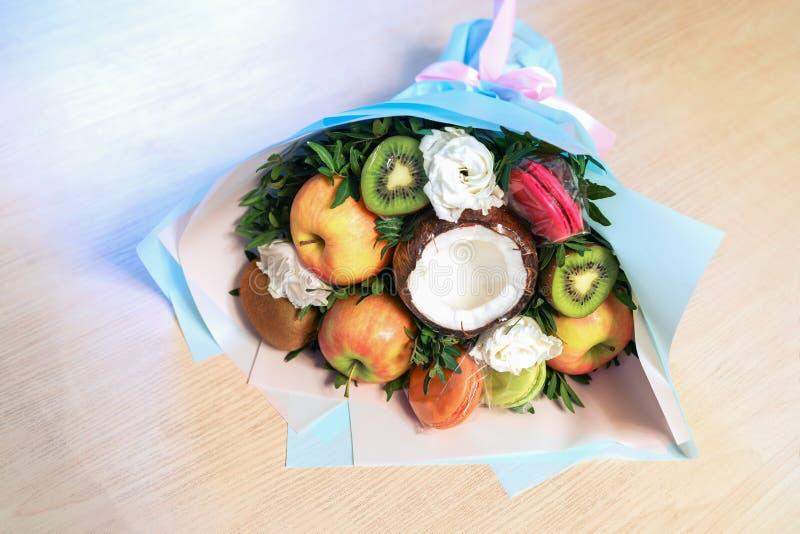 Festlicher verpackter Blumenstrauß von Fruchtmakronen- und -blumenlügen auf Holztisch stockfotos