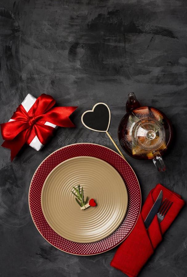 Festliches Gedeck für Valentinstag mit Gabel, Messer und Herzstift mit Rosmarin an den Platten auf einer schwarzen Tabelle Beschn stockbilder
