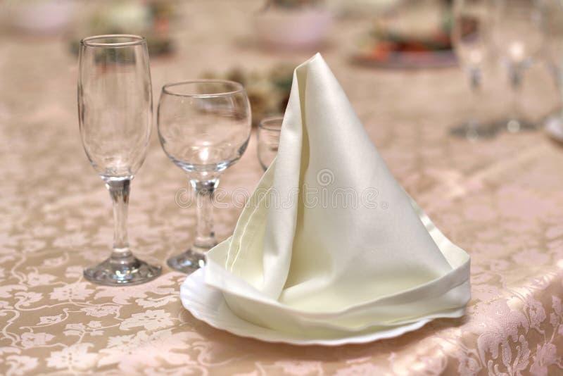 Festliches Gedeck, gefaltete Serviette auf einer Platte und glasse drei stockbild