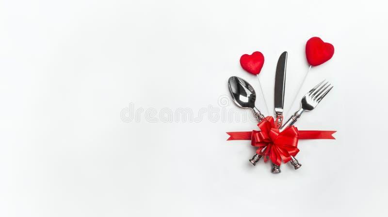 Festliches Tabellengedeck mit rotem Bogen, Tischbesteck und zwei Herzen auf weißem Hintergrund, Fahne Plan für Valentinsgrußtages lizenzfreies stockbild