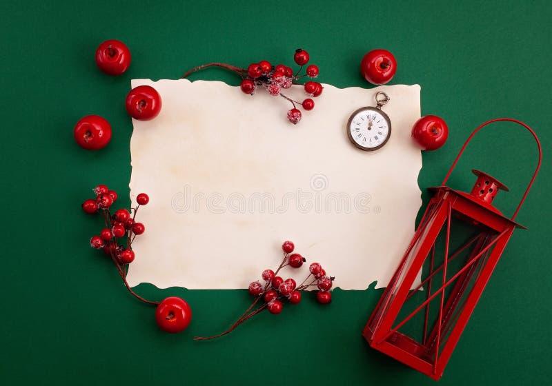 Festliches Weihnachtsmodell über dem grünen Hintergrund mit roter Dekorations- und Weinleseuhr stockfotografie