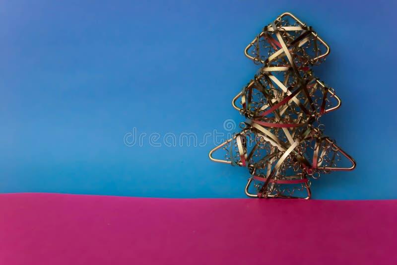 Festliches Weihnachtsweihnachtsglücklicher blau-rosa froher Hintergrund mit einem kleines Spielzeugmetalleisen goldenen selbst ge stockfoto