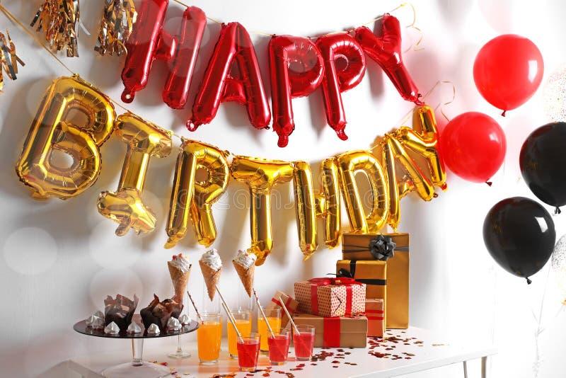 Festlichkeiten und Geschenke auf Tabelle im Raum verziert für Geburtstagsfeier mit Ballonen lizenzfreie stockfotos