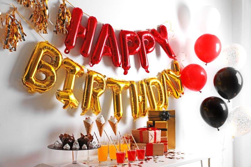 Festlichkeiten und Geschenke auf Tabelle im Raum verziert für Geburtstagsfeier stockbilder
