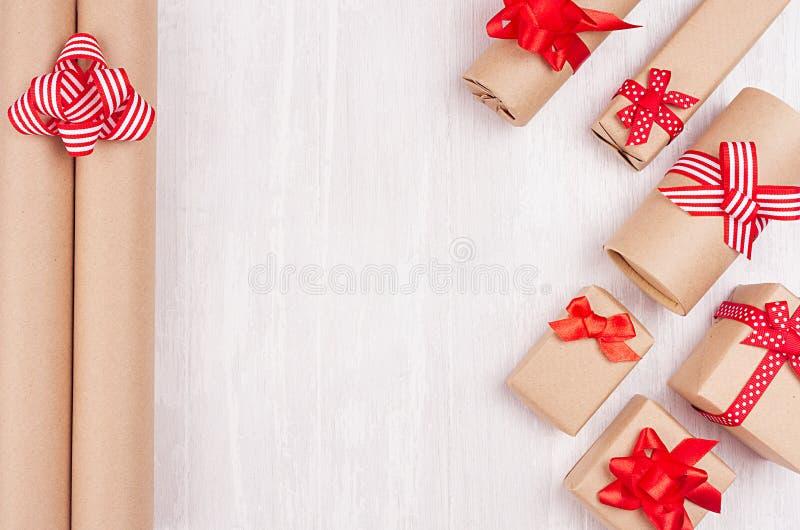 Festlig bakgrund för jul av gåvaaskar med rött pilbåge-, garnering- och rullkraft papper på det mjuka vita träbrädet, kopieringsu royaltyfria foton
