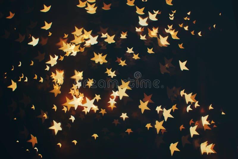 Festlig bakgrund med naturlig bokeh och ljusa guld- ljus Magisk bakgrund för tappning med färg royaltyfria bilder