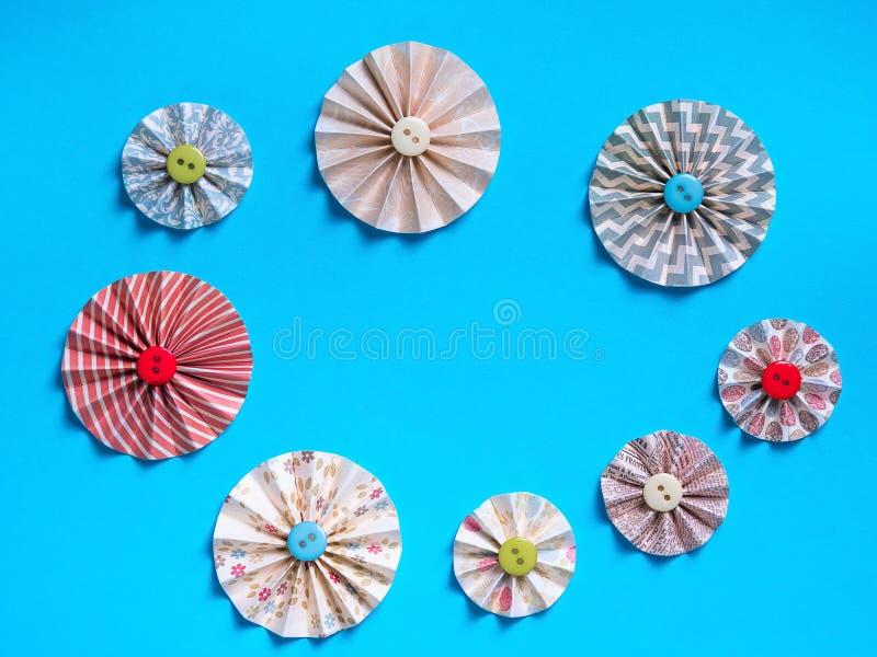 Festlig blå bakgrund med dekorativa handgjorda blommor från knappar och kulört papper arkivbild