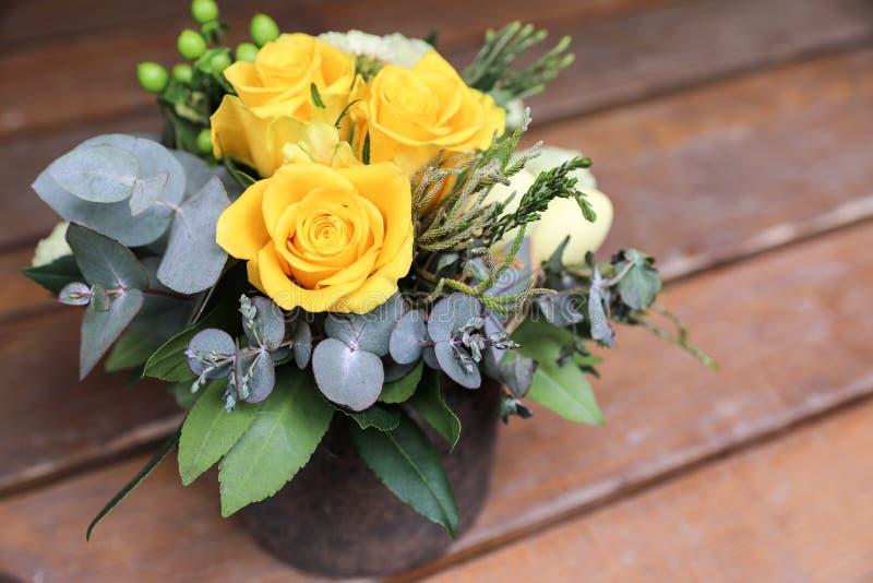Festlig blommaordning av gula rosor, eukalyptussidor och andra växter på träbakgrund arkivbilder