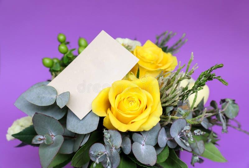 Festlig blommaordning av gula rosor och andra växter med det klara kortet för text på violett bakgrund fotografering för bildbyråer