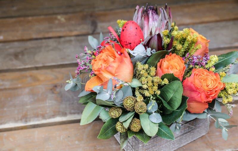 Festlig blommaordning av orange rosor, proteablomman, eukalyptussidor och andra växter med röda påskägg som dekoreras på arkivbild