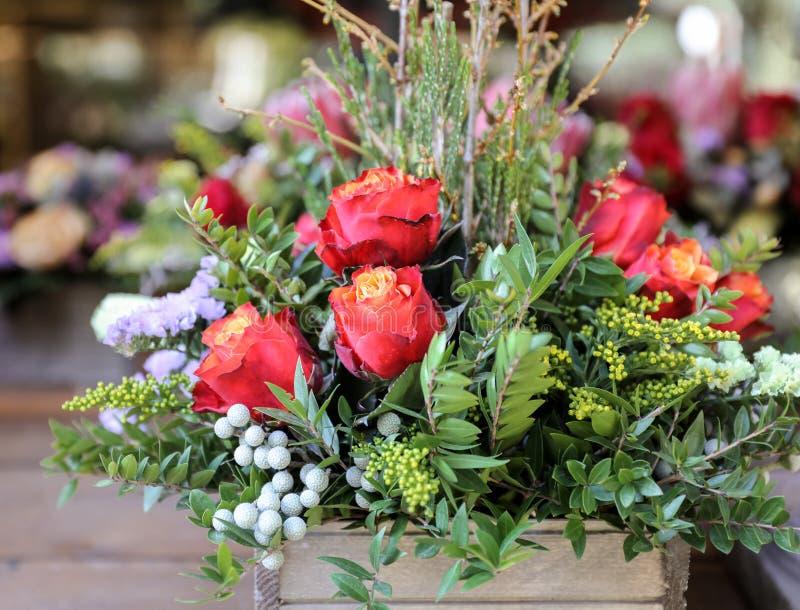 Festlig blommaordning av röda rosor och andra växter royaltyfri foto