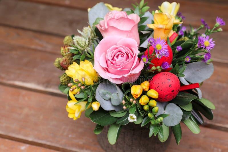 Festlig blommaordning av rosa rosor, gula freesiablommor, eukalyptussidor och andra växter med röda påskägg arkivbild