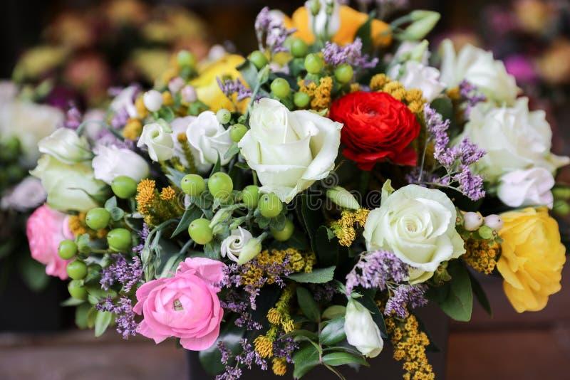 Festlig blommaordning av vit rosor och eustoma, färgrika persiska smörblommablommor och andra växter arkivfoto