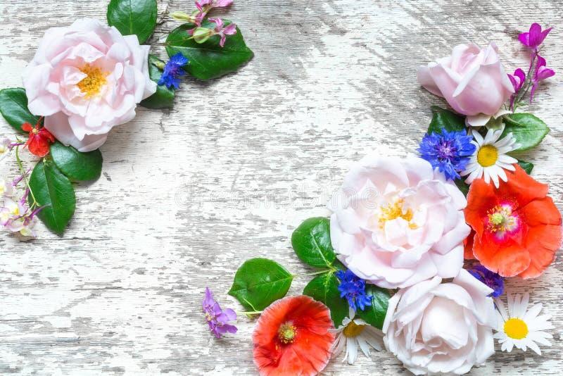 Festlig blommasammansättning av vildblommor, rosor, vallmo och kamomillen på den vita träbakgrunden arkivfoton