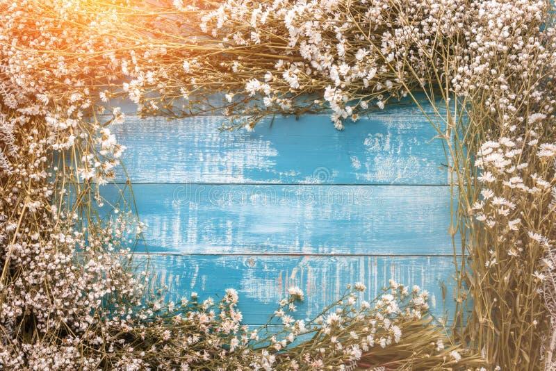 Festlig blommasammansättning med hälsningkortet på den vita wooden royaltyfri bild
