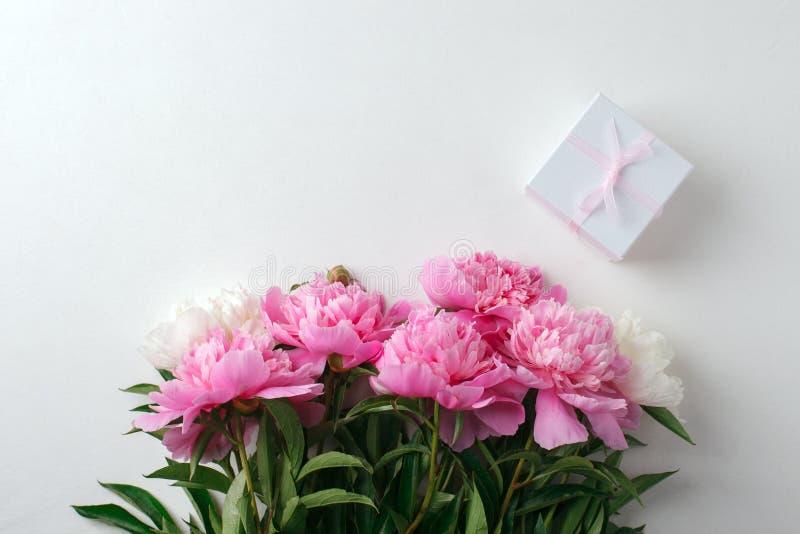 Festlig blommasammansättning på den vita träbakgrunden - rosa pionblommor och giftbox ?ver huvudet sikt säsongsbetonad valentinda royaltyfria foton