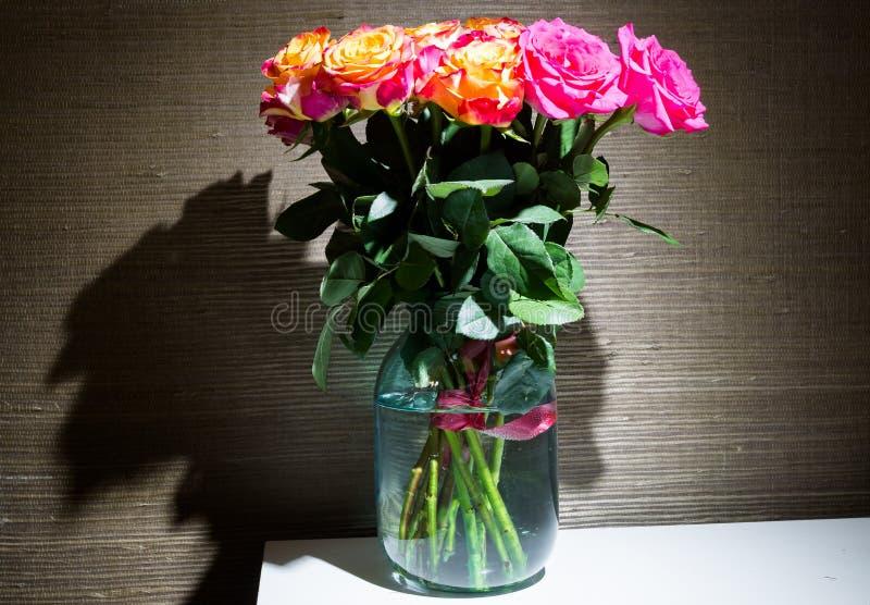Festlig bukett av nya rosor med gul och karmosinröd färgning för original i den glass kruset royaltyfria foton
