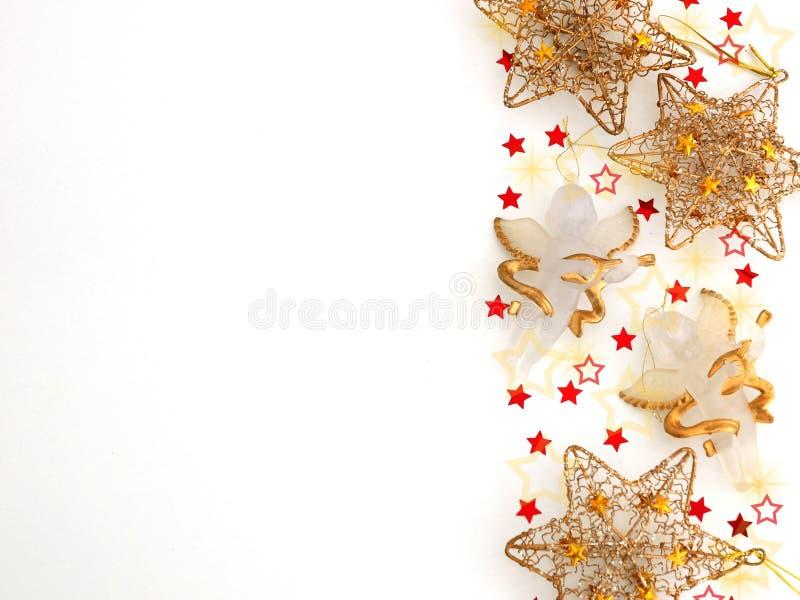 Festlig garnering av guld- stjärnor och änglar på en vit bakgrund arkivbilder
