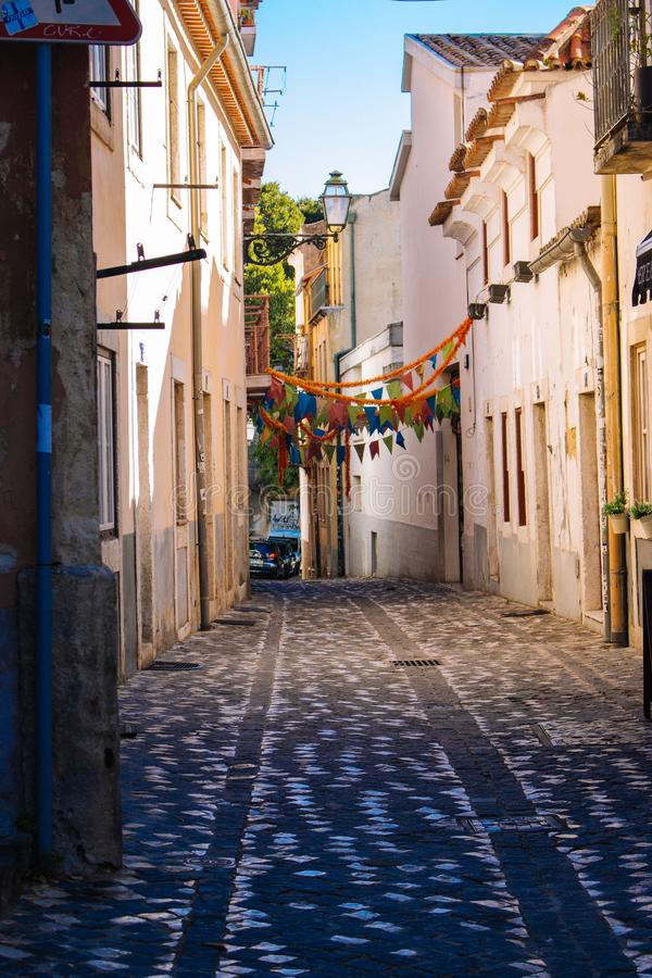 Festlig gatagarnering i Lissabon, Portugal Smal medeltida gata med blommagirlander och flaggor Gammal vit vägg med det stängda fö royaltyfria bilder